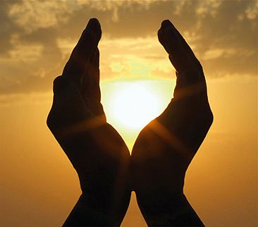 manos orando y con el sol en medio