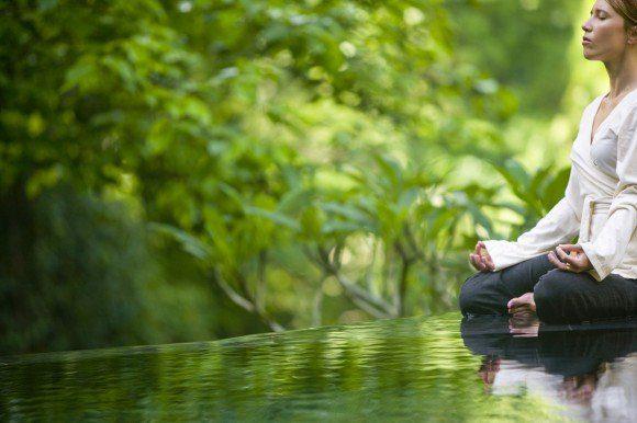 Mujer meditando en la naturaleza con árboles
