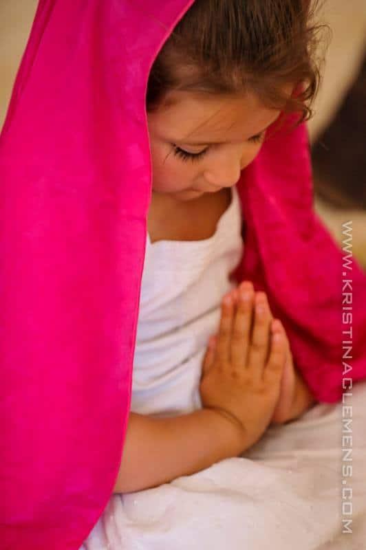 Niña rezando y una manta rosa