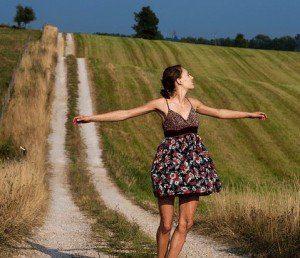 mujer con los brazo abiertos en el campo