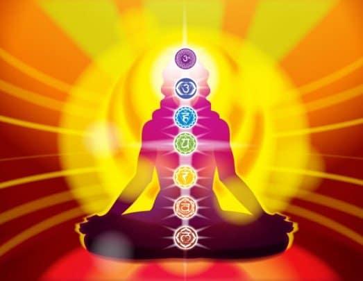 mujer sentada en posicion loto y con todos los chakras