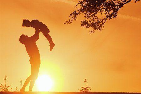 Padre levantando a su hijo en brazos con el sol