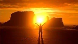 Salida del sol con hombre brazos abiertos