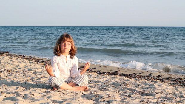 niña-meditando-playa-mar-sol