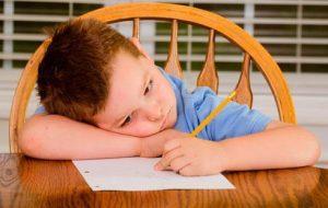 niño escribiendo con cara triste