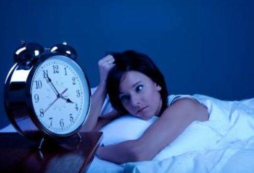 mujer al lado de un reloj trastorno_del_sueño