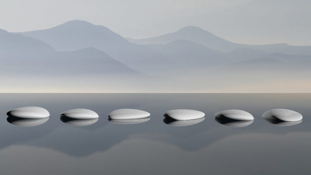 Lake with mountain reflections and Zen stones in the water
