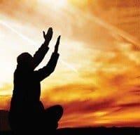 hombre con manos hacia arriba iluminado por el sol