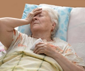 Sick senior woman lying at bed