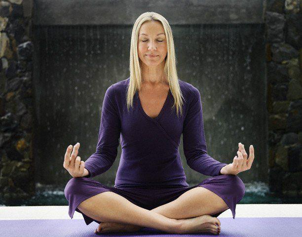 05 Jul 2006 --- Woman Meditating on Yoga Mat --- Image by © B. Bird/zefa/Corbis
