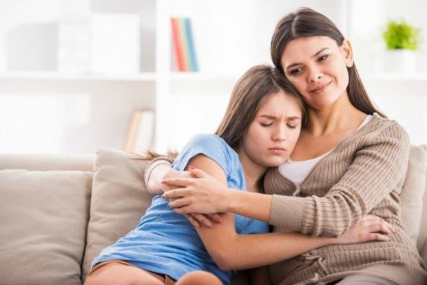 Mother and teen daughter are hugging after quarrel on sofa at home. - Superar a un padre Tóxico parte II: Crecí con una madre asfixiante - hermandadblanca.org