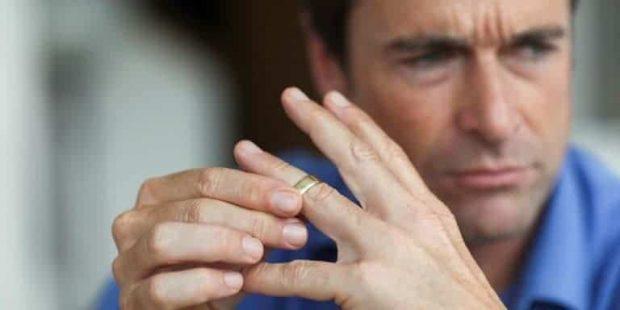 Mature man toying with gold wedding ring on finger - Cómo superar un divorcio parte I: ¿Qué sentimientos esperar? - hermandadblanca.org