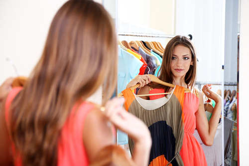 Beautiful girl trying dress near mirror on room background - hermandadblanca.org