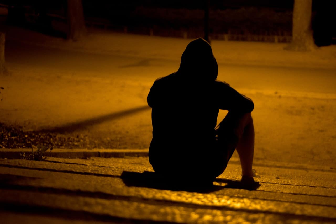 hombre sentado solo en la calle
