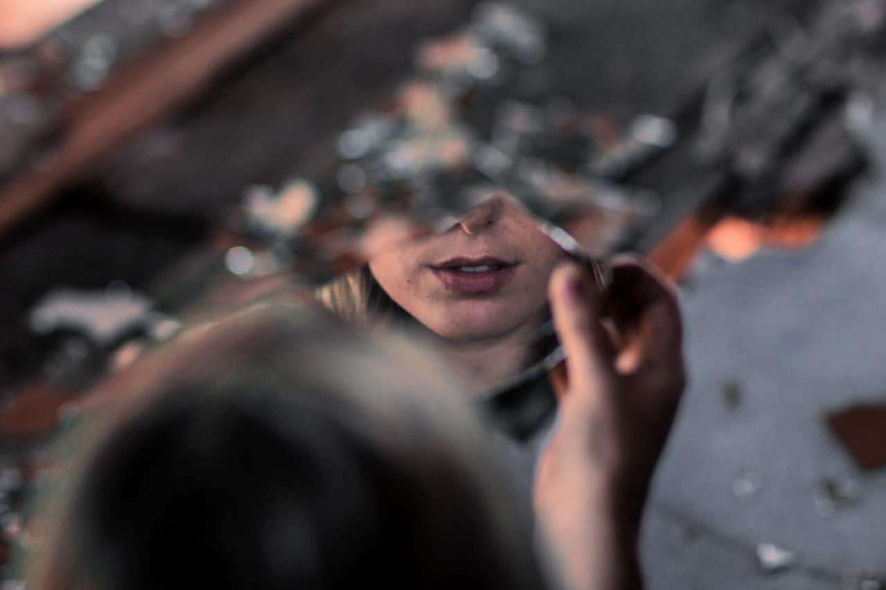 sosteniendo un espejo roto